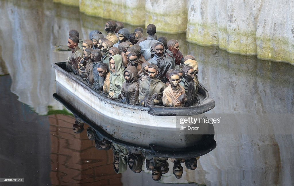 A remote controlled boat by Banksy depicts migrants at the white cliffs of Dover, as Banksy's Dismaland Bemusement Park opens to the public, on August 28, 2015 in Weston-Super-Mare, England. Graffiti artist Banksy has opened the subversive, pop-up theme park styled exhibition at the derelict seafront Tropicana lido, featuring the work of 50 artists. The 'Bemusement Park' combines dark humour and 'entry-level anarchism' and will open for just five weeks.