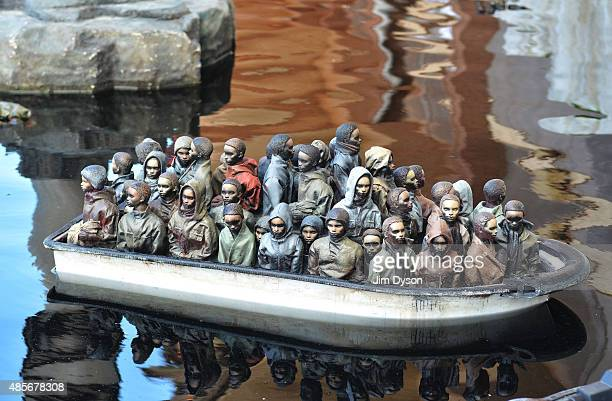 A remote controlled boat by Banksy depicts migrants at the white cliffs of Dover as Banksy's Dismaland Bemusement Park opens to the public on August...
