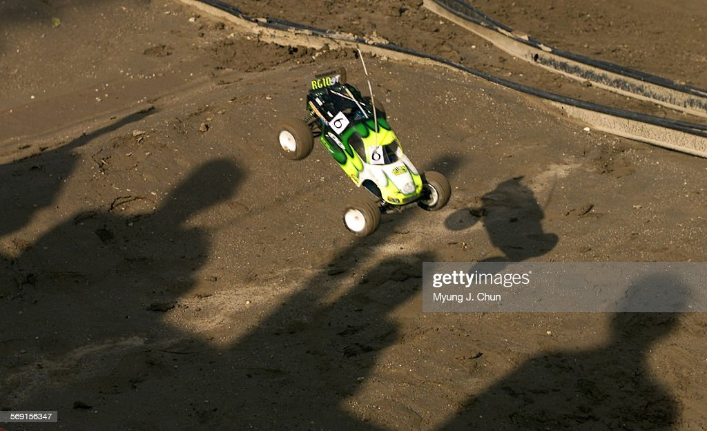 A remote controlled car comes down for a landing on the shadows of drivers during a practice run at the Hot Rod Hobbies race track in Saugus Top...
