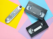Remote, video cassette on a colored pastel background. Retro entertainment technology from the 80s. Minimalism trend. Top view.
