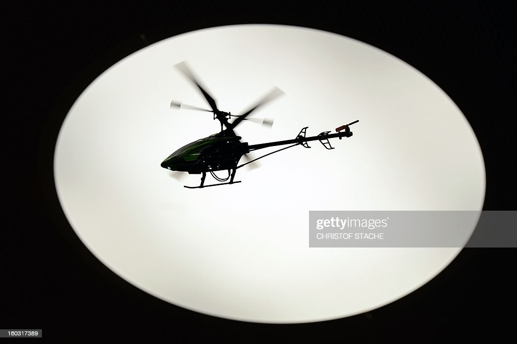 A remote-controlled helicopter flys in front of a light at a booth during the press preview of the international toy fair in Nuremberg, southern Germany, on January 29, 2013. Around 2.700 exhibitors show more than 1 million products at the international toy fair which opens its doors from January 29 to February 4, 2013.