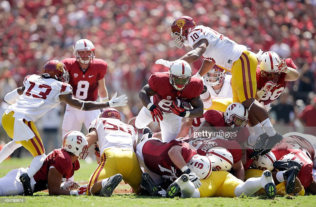 Remound Wright of the Stanford Cardinal dives for a first down as Hayes Pullard of the USC Trojans dives in for the tackle at Stanford Stadium on...