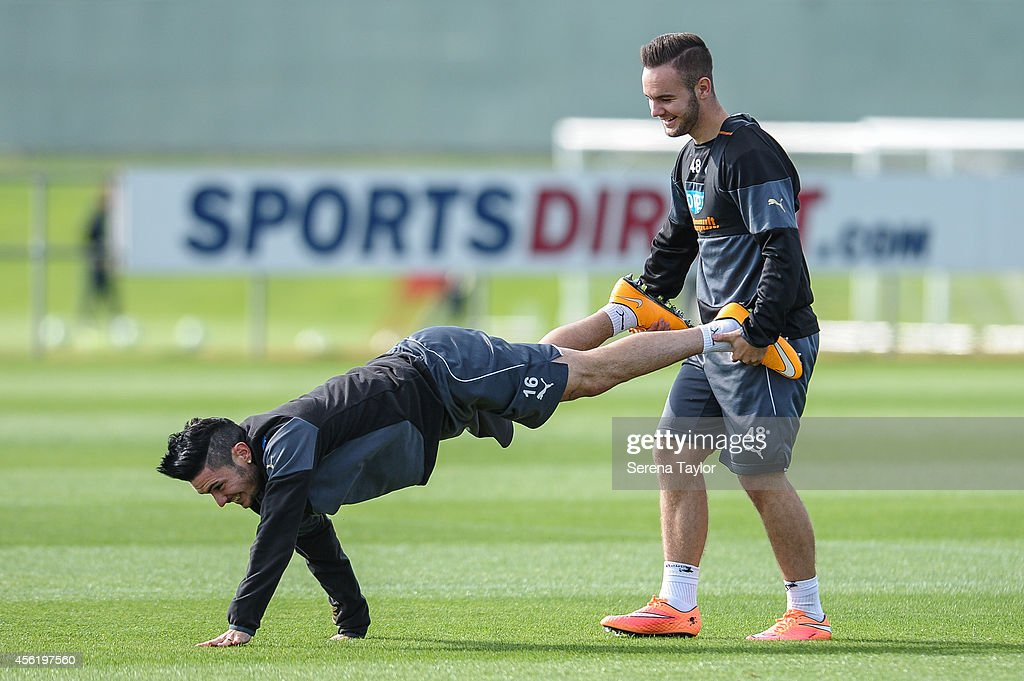 Remy Cabella and Adam Armstrong perform a wheelbarrow during the warm up at the training session at The Newcastle United Training Centre on September 27, 2014, in Newcastle upon Tyne, England.