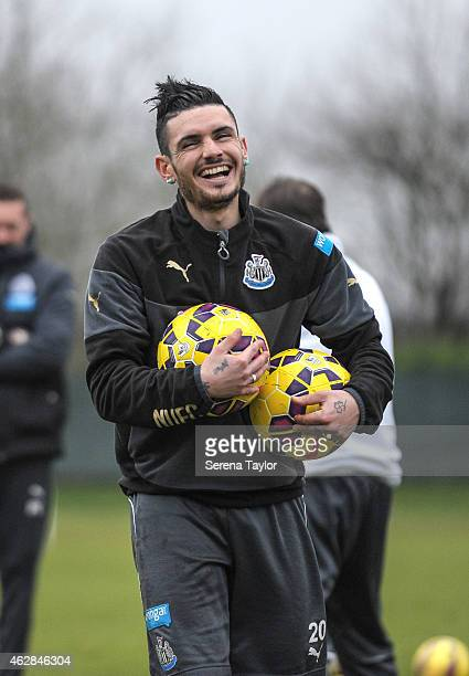 Remy Cabella laughs whilst holding 2 balls in his arms during a training session at The Newcastle United Training Centre on February 06 in Newcastle...