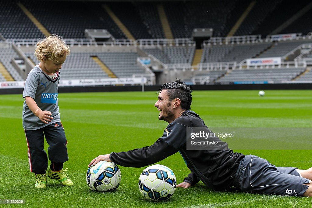 Remy Cabella laughs with a team mates child during a Newcastle United Training Session at St.James Park on August 29, 2014, in Newcastle upon Tyne, England.