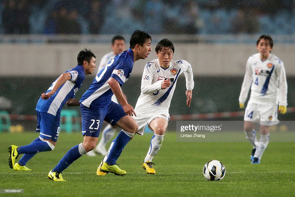 Ren Hang (#23) of Jiangsu Sainty challenges Ryang Yong-Gi (2nd-R) of Vegalta Sendaion during the AFC Champions League match between Jiangsu Sainty and Vegalta Sendai at Nanjing Olympic Sports Center Stadium on March 12, 2013 in Nanjing, China.
