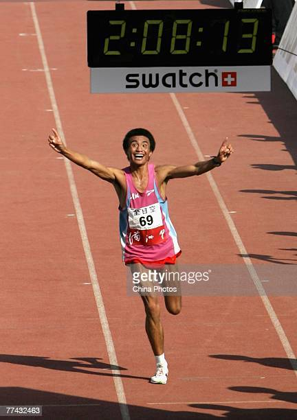 Ren Longyun of China celebrates as he crosses the line to finish second in the men's race at the 2007 Beijing International Marathon on October 21...