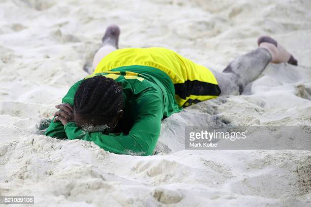 Rena Gordon of Jamaica lies dejected on the sand after defeat in the girl's beach soccer gold medal final match between Trinidad Tobago and Jamaica...