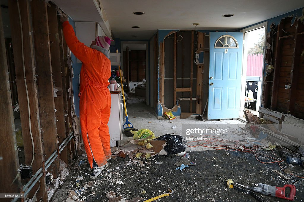 Rena McCain guts out the first floor of her home after it was flooded by Superstorm Sandy on November 25, 2012 in Seaside Heights, New Jersey. New Jersey Gov. Christie estimated that Superstorm Sandy cost New Jersey $29.4 billion in damage and economic losses.