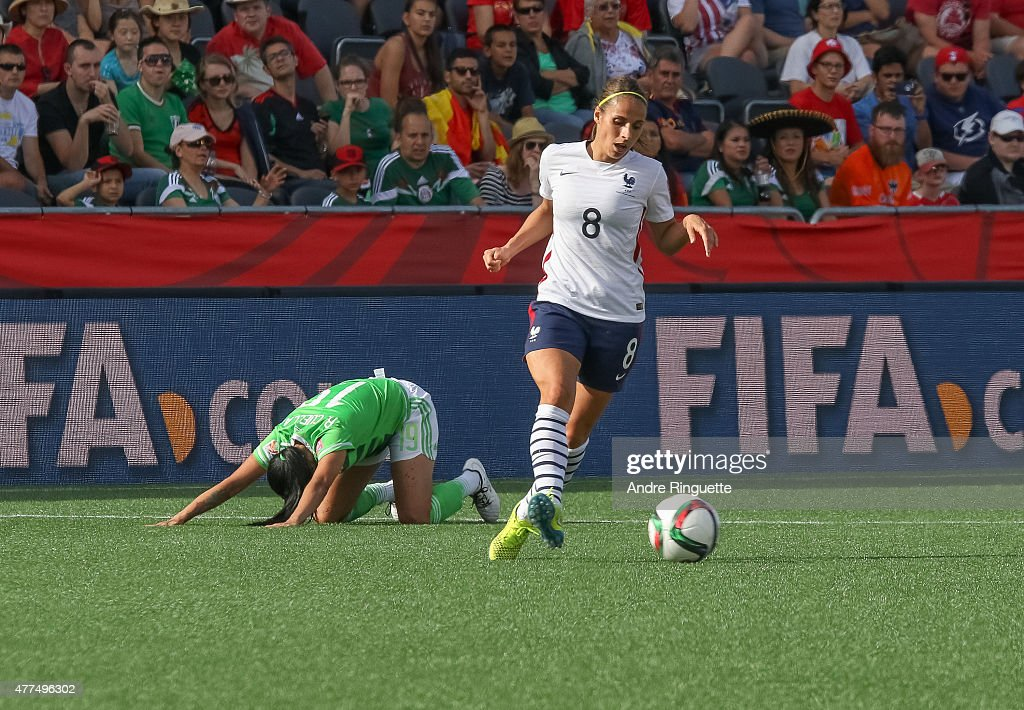Renae Cuellar #19 of Mexico kneels injured on the pitch as <a gi-track='captionPersonalityLinkClicked' href=/galleries/search?phrase=Jessica+Houara&family=editorial&specificpeople=6380286 ng-click='$event.stopPropagation()'>Jessica Houara</a> #8 of France dribbles the ball away during the FIFA Women's World Cup Canada 2015 Group F match between Mexico and France at Lansdowne Stadium on June 17, 2015 in Ottawa, Canada.
