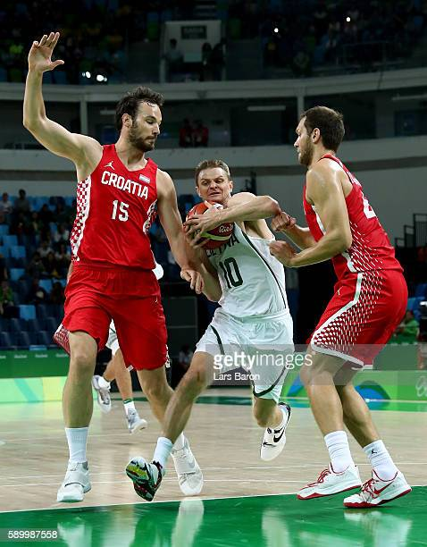 Renaldas Seibutis of Lithuania is challenged by Miro Bilan of Croatia and Bojan Bogdanovic of Croatia during a Men's Basketball Preliminary Round...