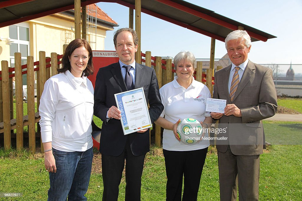 Renate Lingor (L),Prof. Klaus-Michael Debatin (2ndL), Elvira Waeckerle (2ndR) and Norbert Laske (R) attends a donation ceremony on April 8, 2010 in Ulm, Germany. The DFB donates 17.000 � for a children cancer hospital to built a playground.