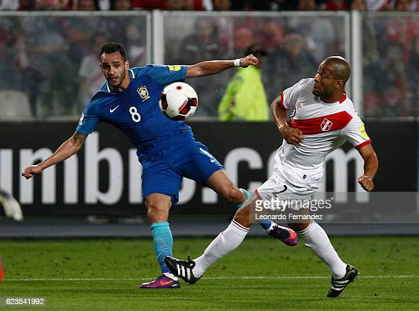 Renato Augusto of Brazil kicks the ball as Alberto Rodriguez of Peru tries to defend during a match between Peru and Brazil as part of FIFA 2018...