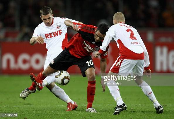 Renato Augusto of Leverkusen and Lukas Podolski battle for the ball as his team mate Miso Brecko of Koeln looks on during the Bundesliga match...