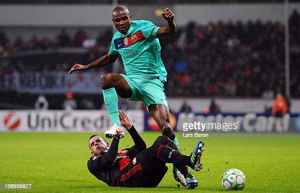 Renato Augusto of Leverkusen challenges Eric Abidal of Barcelona during the UEFA Champions League round of 16 first leg match between Bayer 04...