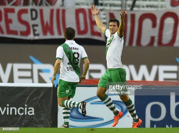 Renato Civelli of Banfield celebrates with teammate Mauricio Sperduti after scoring the first goal of his team during a match between River Plate and...