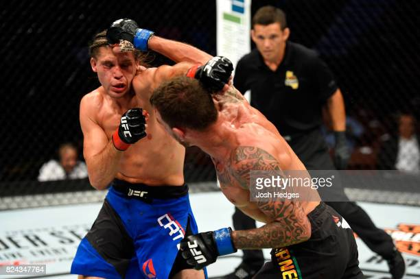 Renato Moicano of Brazil and Brian Ortega trade punches in their featherweight bout during the UFC 214 event at Honda Center on July 29 2017 in...