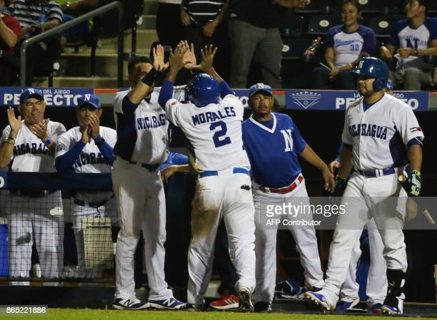 Renato Morales of the Nicaraguan National Baseball Team greets nicaraguan team after scoring in the third inning during a friendly game of the...