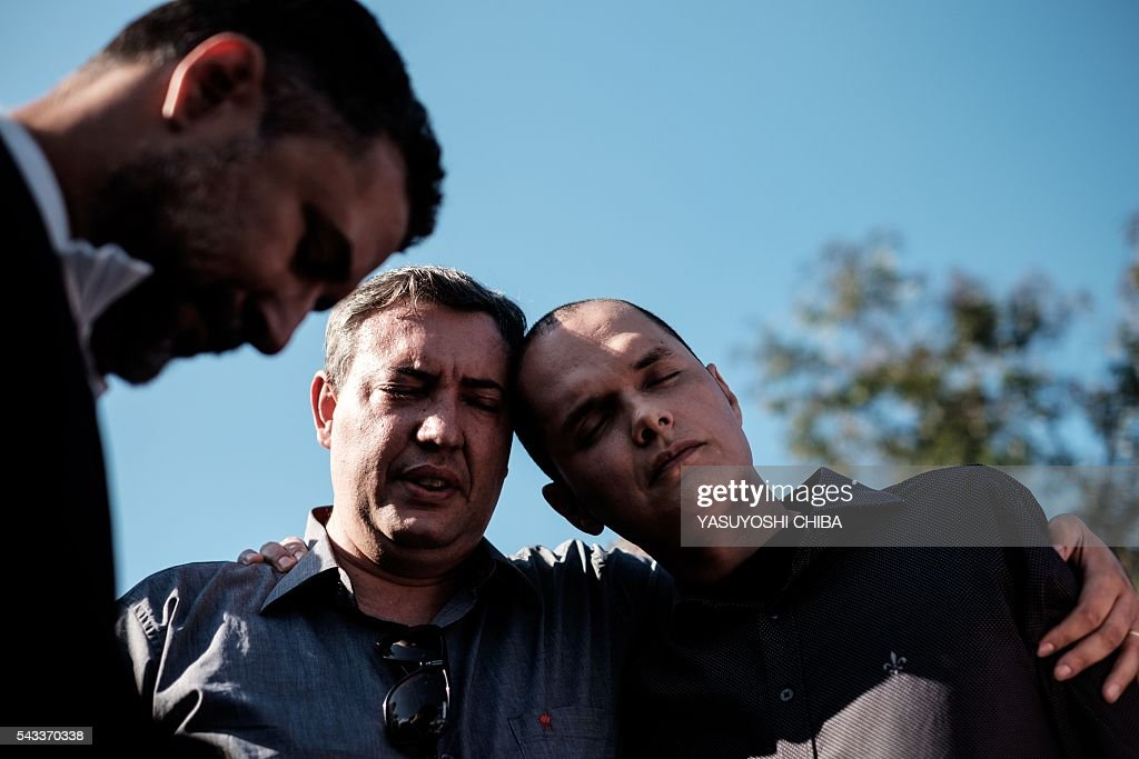 Renato Palhares (R), husband of Gisele Palhares Gouvea -murdered on June 25- is comforted by a pastor during her funeral in Rio de Janeiro, Brazil, on June 27, 2016. Brazilian 34-year-old doctor Gisele Palhares Gouvea was shot in the head inside her SUV as she drove home after attending the inauguration of the service center for handicapped people in northern Rio de Janeiro. / AFP / YASUYOSHI