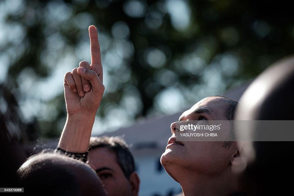 Renato Palhares, husband of Gisele Palhares Gouvea who was murdered on June 25, points his finger to the sky during the funeral in Rio de Janeiro, Brazil, on June 27, 2016. Brazilian 34-year-old doctor Gisele Palhares Gouvea was shot in the head inside her SUV as she drove home after attending the inauguration of the service center for handicapped people in northern Rio de Janeiro. / AFP / YASUYOSHI