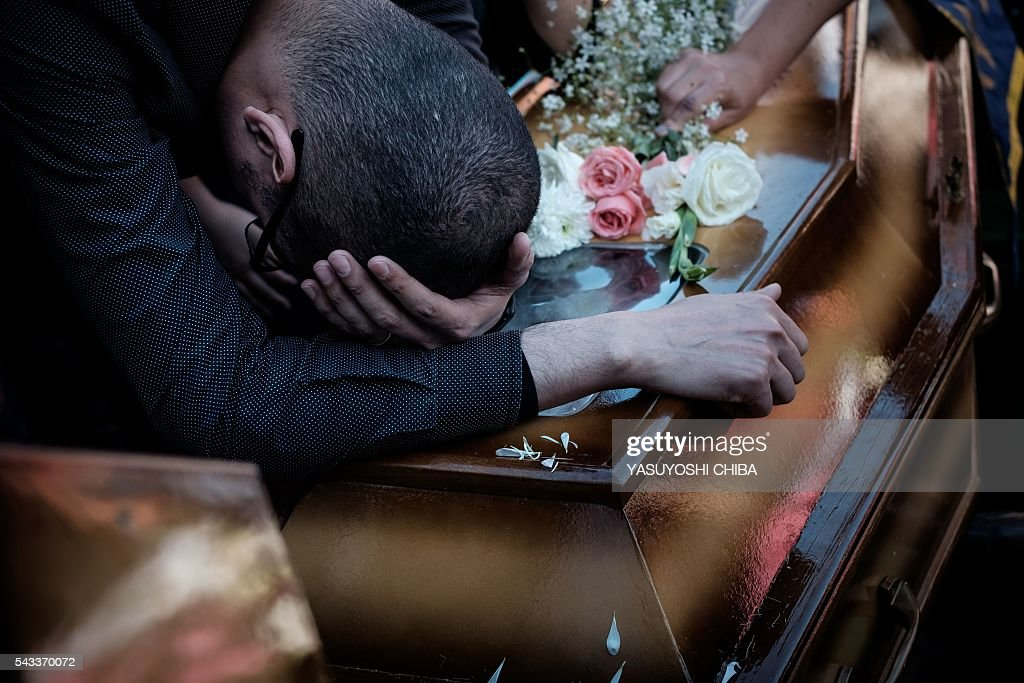 Renato Palhares, husband of Gisele Palhares Gouvea who was murdered on June 25, mourns over her coffin during her funeral in Rio de Janeiro, Brazil, on June 27, 2016. Brazilian 34-year-old doctor Gisele Palhares Gouvea was shot in the head inside her SUV as she drove home after attending the inauguration of the service center for handicapped people in northern Rio de Janeiro. / AFP / YASUYOSHI