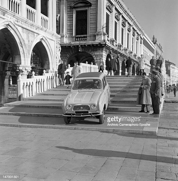 A Renault 4L car getting down the bridge called 'Ponte della Paglia' near 'Riva degli Schiavoni' Venice 1961