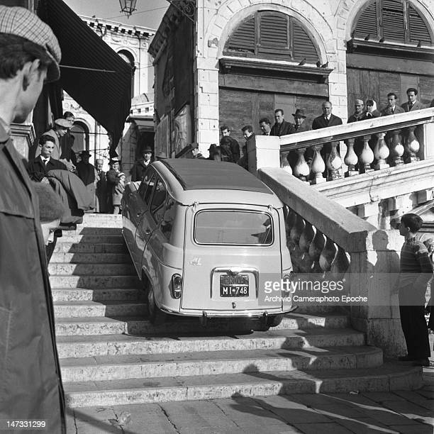 A Renault 4L car getting up the stairs of Rialto Bridge Venice 1961