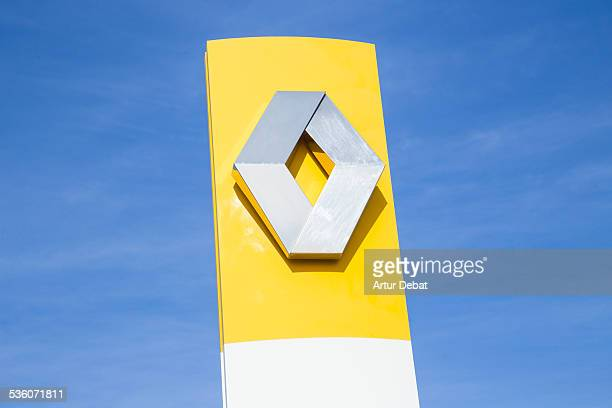 Renault logo trademark with yellow color and blue sky in a car dealer