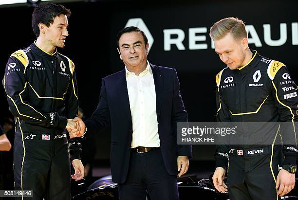 Renault President Carlos Ghosn shakes hands with British driver Jolyon Palmer next to Danish Formula One driver Kevin Magnussen during the official...
