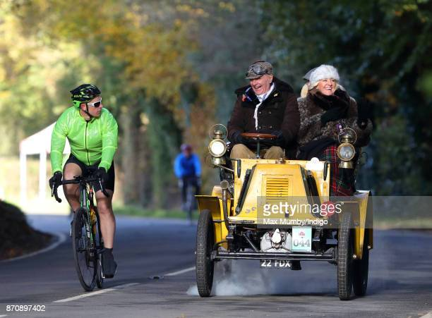 A 1900 Renault Tonneau is overtaken by a cyclist as it takes part in the annual London to Brighton Veteran Car Run on November 5 2017 in Staplefield...