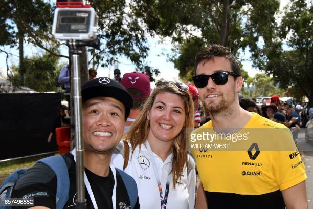 Renault's British driver Jolyon Palmer poses for a selfie with fans before the third practice session at the Formula One Australian Grand Prix in...