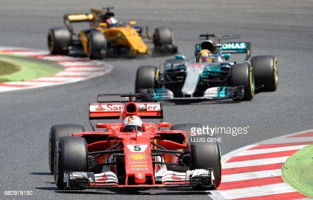 Renault's German driver Nico Hulkenberg Mercedes' British driver Lewis Hamilton and Ferrari's German driver Sebastian Vettel race at the Circuit de...