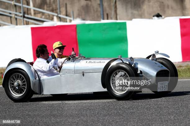 Renault's German driver Nico Hulkenberg rides in a classic car during the drivers' parade for the Formula One Japanese Grand Prix in Suzuka on...