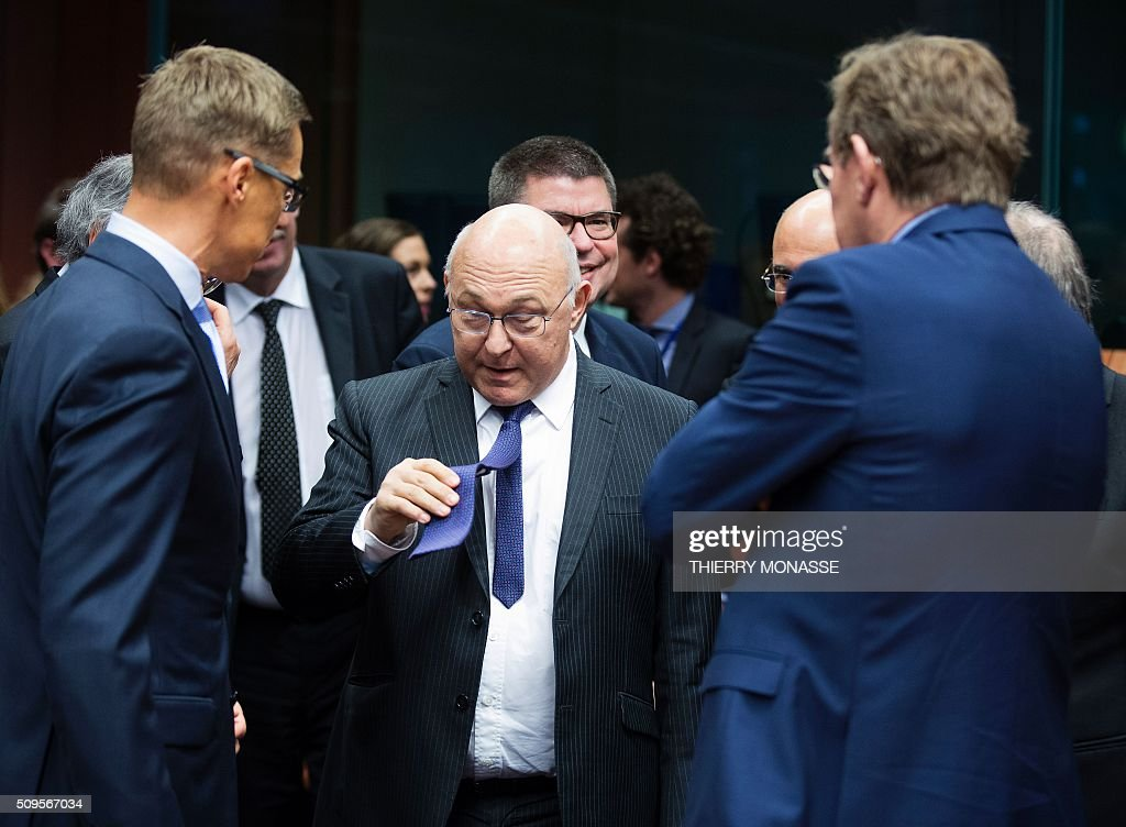 rench Finance and Public Accounts Minister Michel Sapin (C) shows his tie as he talks with Finnish Finance Minister Alexander Stubb (L) and the Belgian Finance Minister Johan Van Overtveldt (R) prior to a meeting of Eurogroup ministers at the European Council headquarters in Brussels on February 11, 2016. / AFP / THIERRY MONASSE