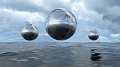 3D illustration of transparent liquid balls hoovering above water. A close-up of abstract organic elements. Silver shiny colored textures with a lot of reflection.