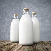 3D rendering glass milk bottles on wooden table.