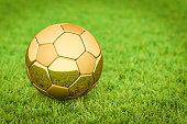 3D rendering: Golden Soccer ball / football lying on grass in a stadium, Big Business in sports, football, soccer.
