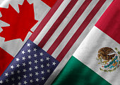 Closeup of the flags of the North American Free Trade Agreement NAFTA members on textile texture. NAFTA is the world's largest trade bloc and the member countries are Canada, United States and Mexico.