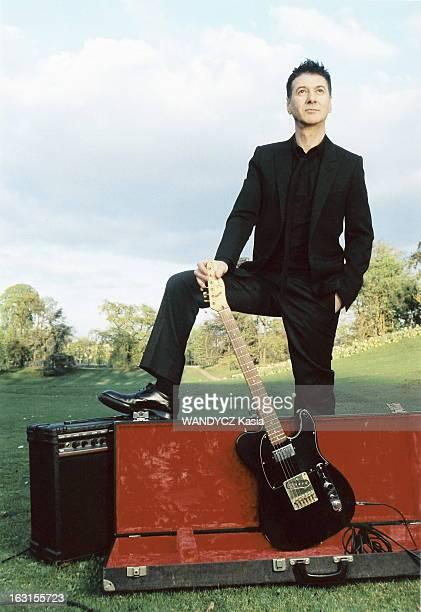 Rendezvous With Etienne Daho Attitude d'Etienne DAHO tenant sa guitare posée dans son étui un pied posé sur l'amplificateur dans un parc