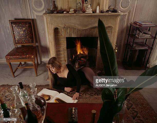 Rendezvous With Helene Rolles En France le 7 février 1993 Hélène ROLLES actrice chanteuse allongée sur un tapis devant une cheminée feuilletant un...