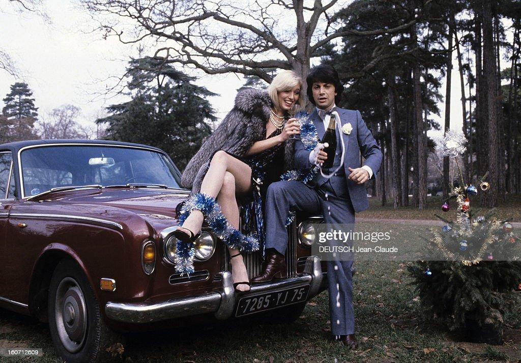Rendezvous With Herve Vilard And Kim Harlow. En France, à Paris, en décembre 1979, Kim HARLOW, chanteuse, et Hervé VILARD, chanteur, buvant du champagne, fêtant noël, assis sur le capot d'une Rolls-Royce.