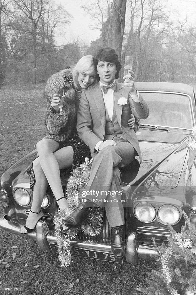 Rendezvous With Herve Vilard And Kim Harlow. En France, à Paris, en décembre 1979, Kim HARLOW, chanteuse, et Hervé VILARD, chanteur, buvant du champagne, fêtant noël, assis sur le capot d'une Rolls-Royce dans la campagne.