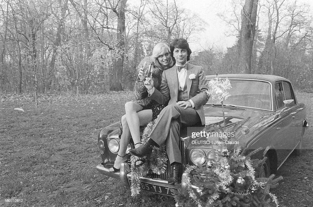 Rendezvous With Herve Vilard And Kim Harlow. En France, à Paris, en décembre 1979, Kim HARLOW, chanteuse, et Hervé VILARD, chanteur, buvant du champagne, fêtant noël, assis sur le capot d'une Rolls-Royce dans la campagne. Un sapin de Noël est posé devant l'automobile.