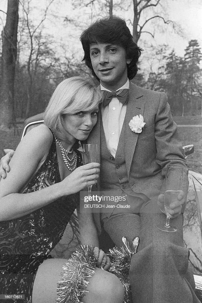 Rendezvous With Herve Vilard And Kim Harlow. En France, à Paris, en décembre 1979, Kim HARLOW, chanteuse, et Hervé VILARD, chanteur, buvant du champagne, fêtant noël, assis sur le capot d'une Rolls-Royce. Une guirlande est posée sur leurs genoux.