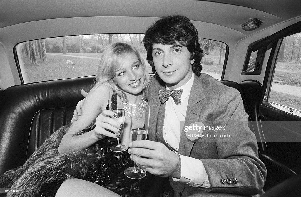 Rendezvous With Herve Vilard And Kim Harlow. En France, à Paris, en décembre 1979, Kim HARLOW, chanteuse, et Hervé VILARD, chanteur, buvant du champagne, fêtant noël, assis à l'intérieur d'une Rolls-Royce : ils trinquent.
