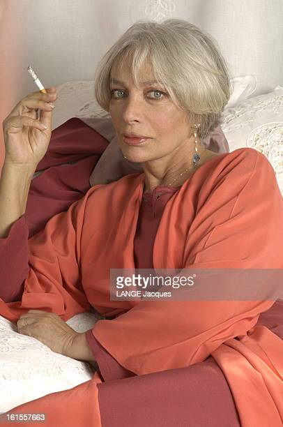 Rendezvous With Marie Laforet Plan de face souriant de Marie LAFORET fumant une cigarette chez elle à PARIS