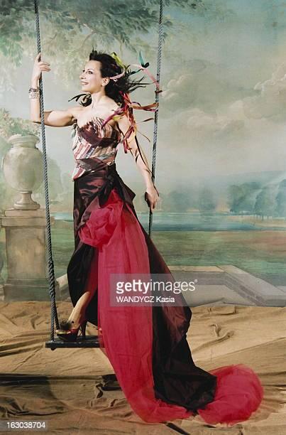 Rendezvous With Natalie Dessay Photo studio attitude souriante de la soprano Natalie DESSAY de profil debout sur une balançoire portant une tenue...