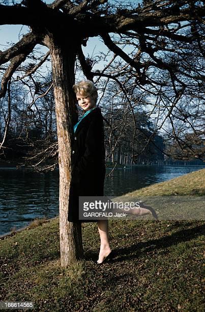 Rendezvous With Noelle Adam Lors d'une séance de portraits dans un parc devant un lac l'actrice Noëlle ADAM en manteau noir s'appuyant contre un arbre