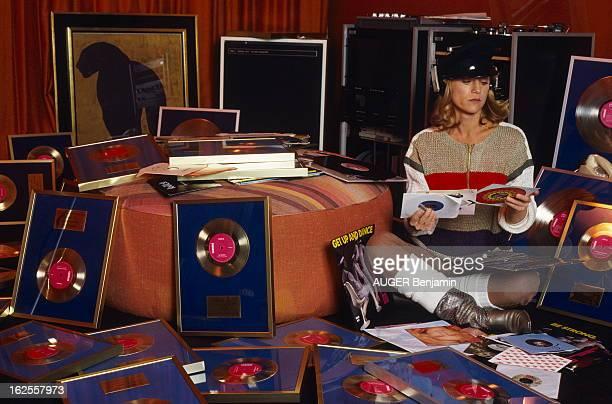 Rendezvous With Sheila Attitude de SHEILA portant une casquette des bottes et des jambières et un casque sur les oreilles regardant de vieux 45 tours...