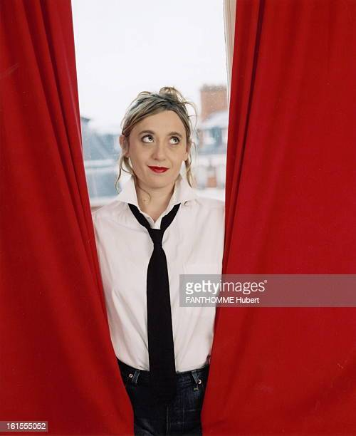 Rendezvous With Virginia Despentes Virginia DESPENTES smiling attitude white shirt and black tie leves eyes to heaven posing between red curtains in...